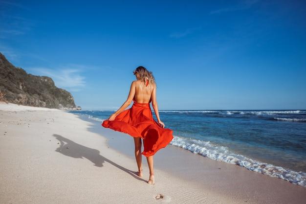Девушка гуляет по пляжу в красном платье, вид сзади