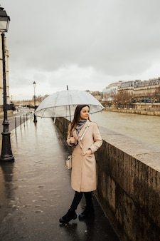 Girl walking on the parisian street near river seine with umbrella on rainy day.