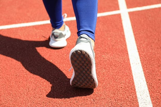 Girl walking on red athletic track, close up