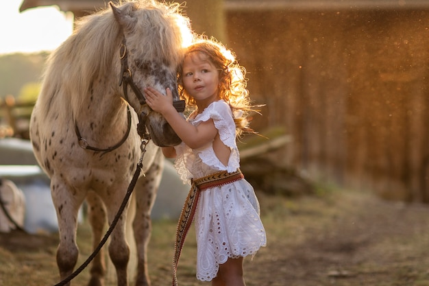 Girl walking at sunset in a field with a horse