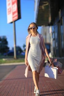 ショッピングバッグを持って歩く女の子。女性の買い物の概念。買い物客。販売。