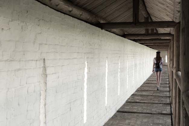 The girl walks along the long aisle of the monastery against the background of a white wall.