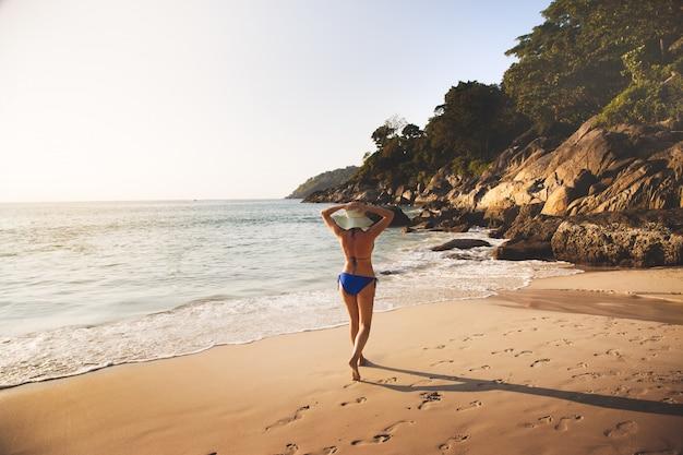 Girl walks along the ocean in the tropics