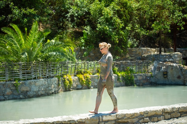 A girl walks along a pool with mud baths at a resort in turkey.health improvement in therapeutic mud