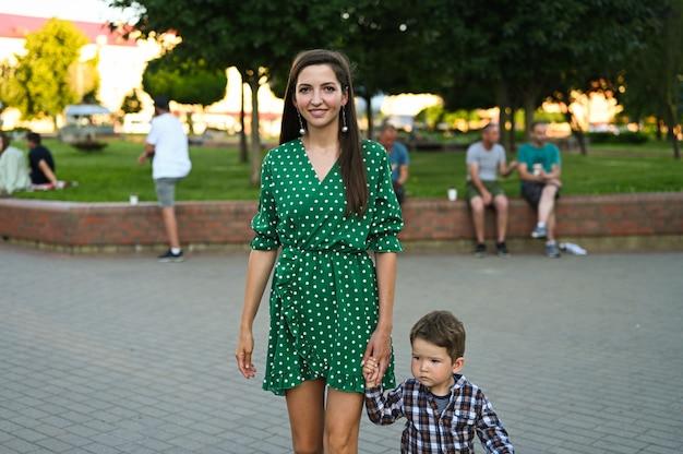 Девушка гуляет по городу, держа за руку ребенка