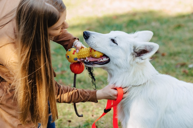 Girl walks at autumn park with young white swiss shepherd dog