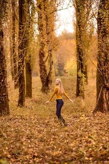 Девушка гуляет в осеннем лесу. молодая женщина крутится на фоне апельсиновых деревьев.