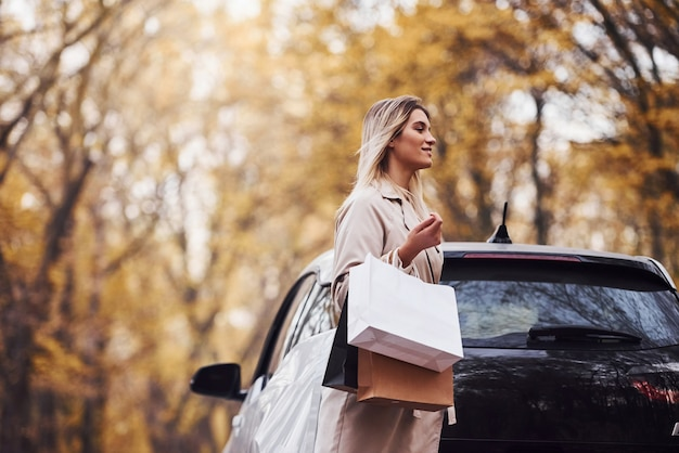 Girl walks near the car with shopping bags in hands. modern brand new automobile in the forest. Premium Photo