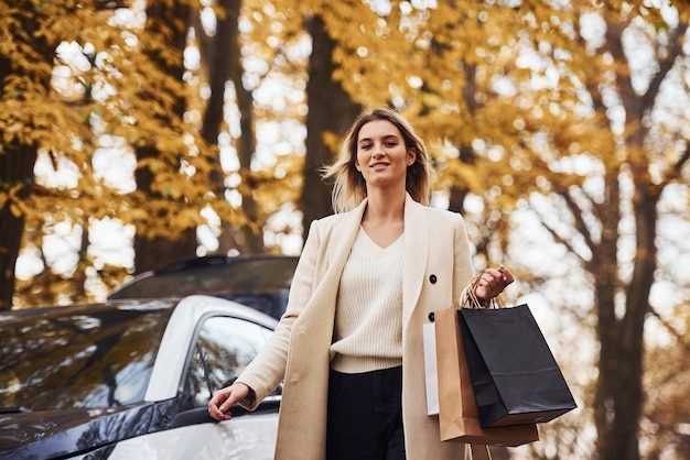 Girl walks near the car with shopping bags in hands. modern brand new automobile in the forest.