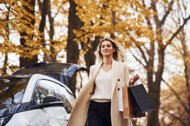 Девушка ходит возле машины с сумками в руках. современный новый автомобиль в лесу.