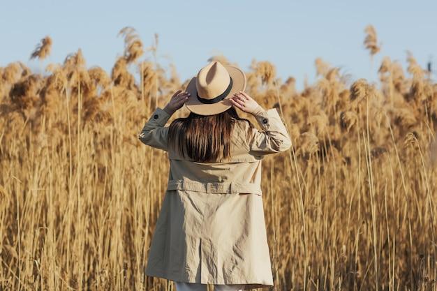 女の子は乾いたふわふわの葦の間で自然の上を歩きます