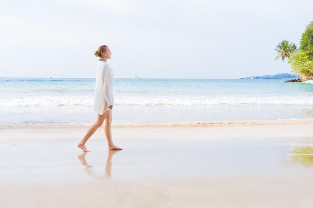 Девушка гуляет по пляжу и в воде