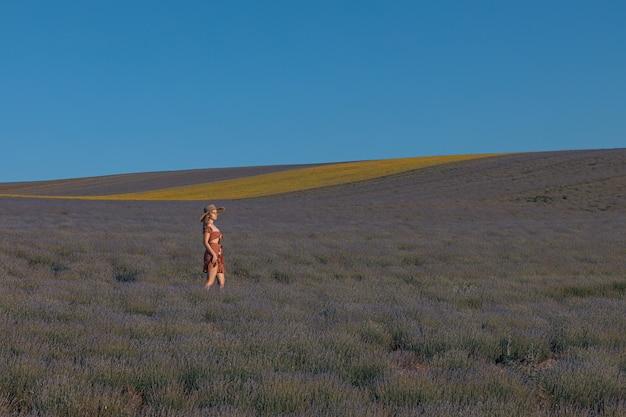 A girl walks through a lavender field