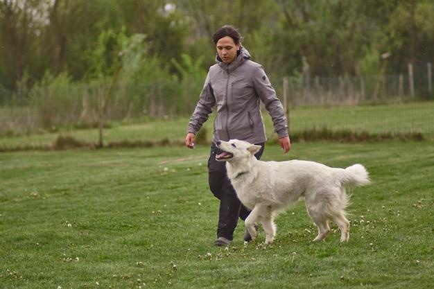 Девушка идет в парк со своей собакой