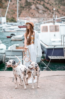 Girl walks with pet, adult dalmatian on the waterfront with water transport