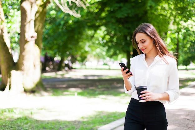 女の子は彼女の手の中で電話と公園でコーヒーの杯を歩く