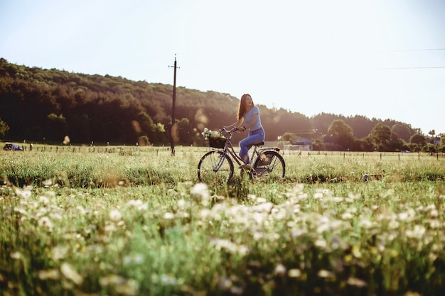 The girl walks with a puppy in a field in a bicycle in the back of sunny light