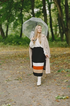 Girl walks. woman in a brown coat. blonde with umbrella.