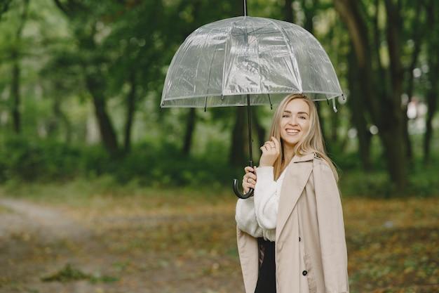 Girl walks. woman in a brown coat. blonde with umbrella.