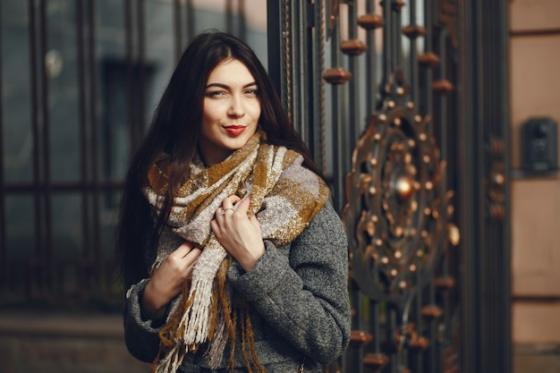 Girl walks. woman in a coat. brunette with a scarf.