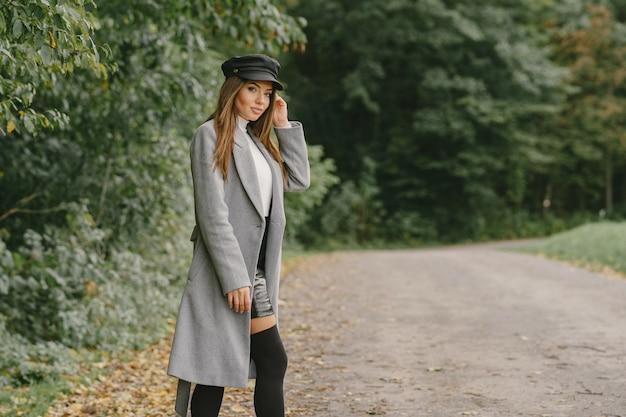 La ragazza cammina. donna in un cappotto grigio. bruna con un berretto nero.