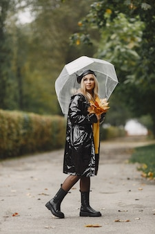 女の子が歩きます。黒いコートを着た女性。黒い帽子をかぶった金髪。傘を持つ女性。