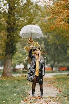 Ходит девушка. женщина в черном пальто. блондинка в черной кепке. дама с зонтиком.