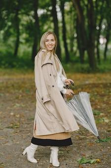 Ходит девушка. женщина в коричневом пальто. блондинка с зонтиком.
