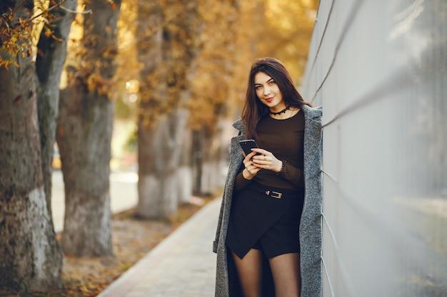 女の子が歩きます。コートを着た女性。女性は携帯電話を使用します。