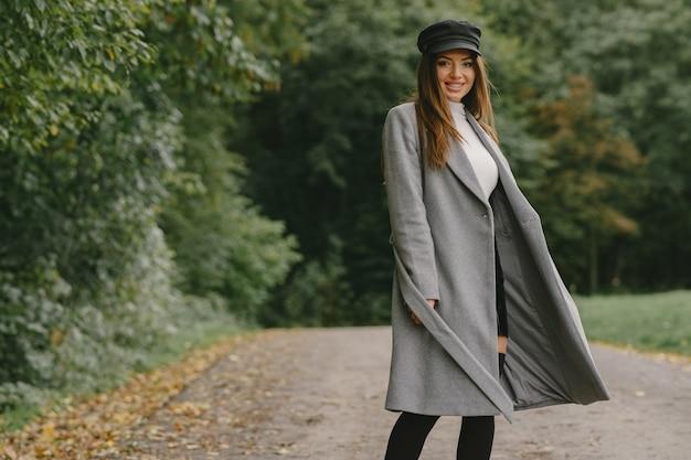 Ходит девушка. женщина в сером пальто. брюнетка в черной кепке.
