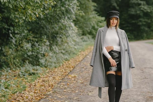 女の子が歩きます。灰色のコートを着た女性。黒帽子のブルネット。