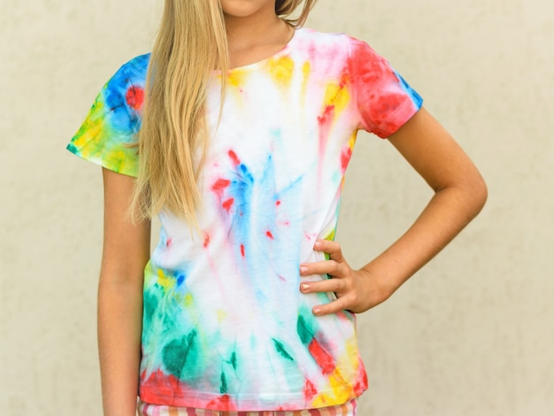 Girl at the wall in a t-shirt painted in the style of tie dye.