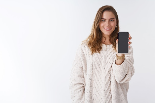 소녀는 당신에게 스마트폰 디스플레이를 보여주는 당신의 의견을 듣고 싶어합니다. 흰색 배경에 활짝 웃고 있는 재미있는 사진을 공유하는 휴대전화를 들고 손을 내밀고 있는 매력적인 매력적인 여성