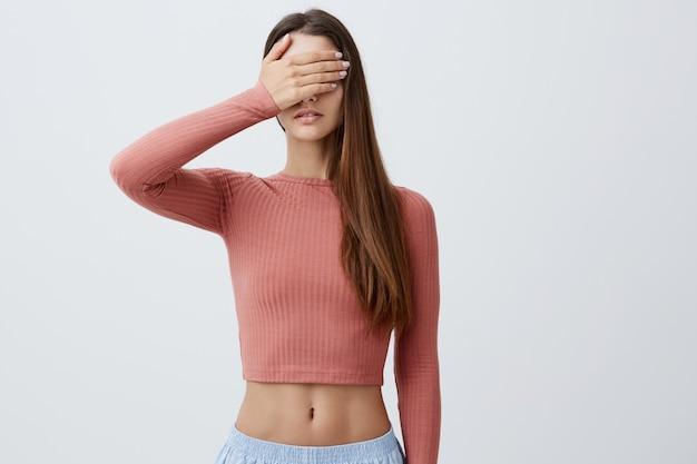 La ragazza non vuole vedere qualcosa. chiuda su di giovane bella studentessa caucasica in occhi alla moda dell'abbigliamento dei vestiti con una mano. linguaggio del corpo.