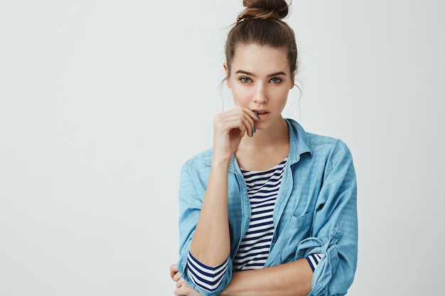 Girl wants to believe boyfriend but knows he is lying. studio shot of suspicious focused woman with bun hairstyle, touching lips while thinking or hearing out excused, standing