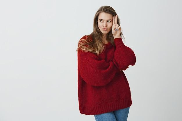 女の子はガールフレンドに電話してパーティーに行きたいです。よそ見しながら顔の近くのvサインを押しながらキスで唇を折りたたむスタイリッシュな冬のセーターで魅力的な女性の女性の肖像画