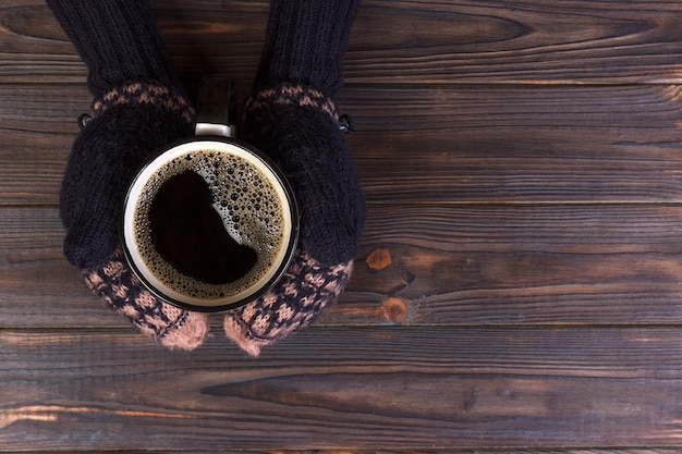 Girl in a warm clothes and mittens is holding white mug in hands.