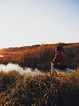 A girl in a warm jacket sits on a pier near the lake and admires the sunset in autumn