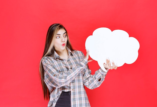 Ragazza con un maglione caldo che tiene in mano un'ideaboard a forma di nuvola e sembra sorpresa