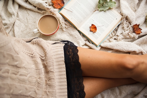 A girl in a warm sweater sits on a beige woolen blanket and holds a mug of hot coffee in her hands.