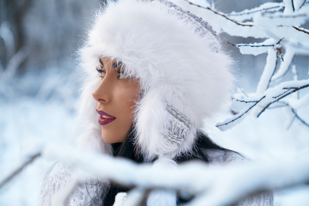 Girl in warm winter hat near branches of trees with snow.