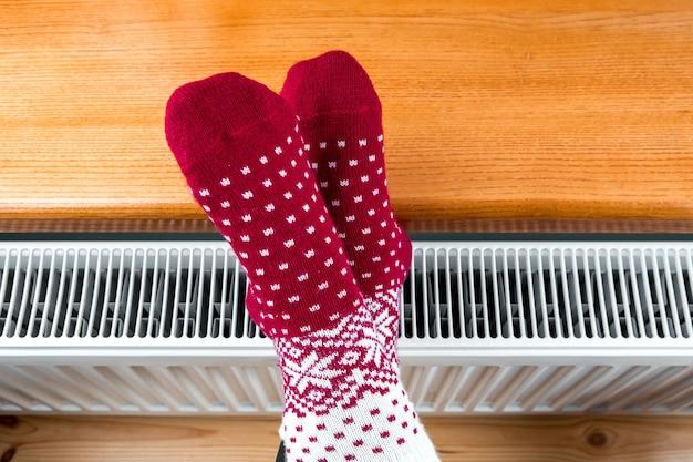 소녀는 라디에이터에 손과 발을 따뜻하게합니다.