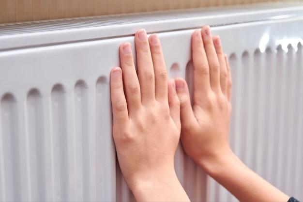 女の子はラジエーターで手を温めます