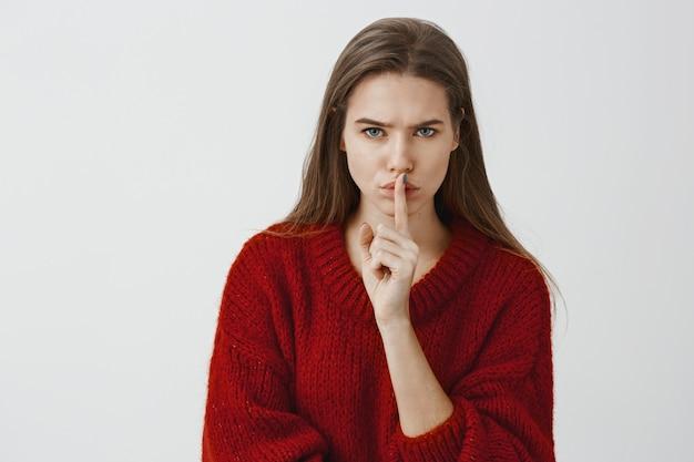 Девушка предупреждает, что мы не должны никому рассказывать ее секрет. крытый выстрел обеспокоенной серьезной привлекательной женщины в красном свободном свитере, shushing, показывая shh знак с указательным пальцем по рту, стоя над серой стеной