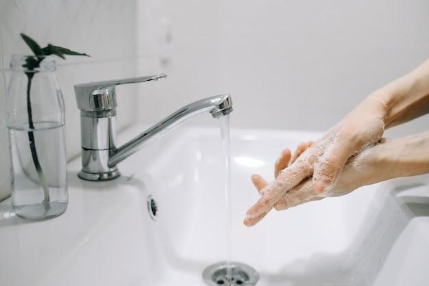 Девушка тщательно моет руки с мылом под водой в белой ванной, вид сбоку концептуальное фото чистоты