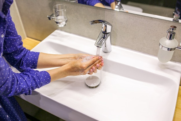 The girl washes her hands with soap a drop of soap wash your hands during a pandemic clean hands washbasin with soap washes her hands with liquid soap beautiful manicure with soap clean hands