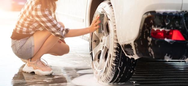 スポンジで車のホイールを洗う女の子
