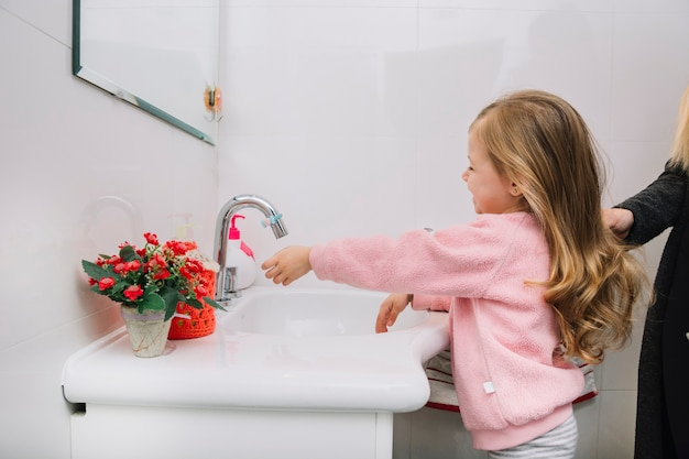 Girl washing her hand in bathroom sink