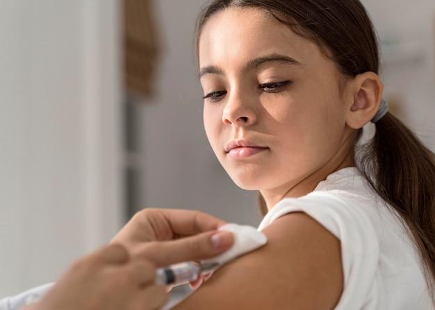 医者が彼女に予防接種をしているのを見ている女の子