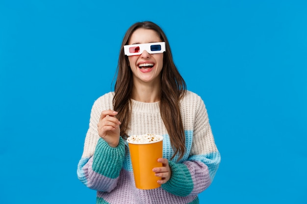 Girl watching comedy in cinema. carefree happy young brunette woman in winter sweater, enjoying funny movie, laughing out loud eating popcorn, wearing 3d glasses, standing blue wall